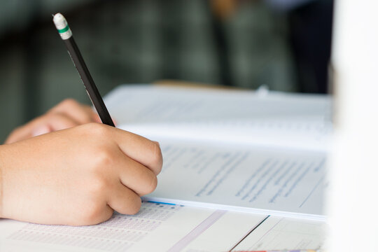 Exams test student in high school, university student holding pencil for testing exam writing answer sheet and exercise for taking in assessment paper on wood table classroom. Education study Concept