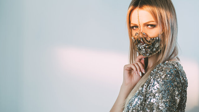 Pandemic fashion. Quarantine accessory. Festive trend 2021. Portrait of woman in glamour chain gem face mask matching shiny sequin dress on blur blue pink light copy space background.