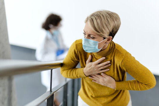 Woman with protective face mask holding her chest in pain at hospital hallway.