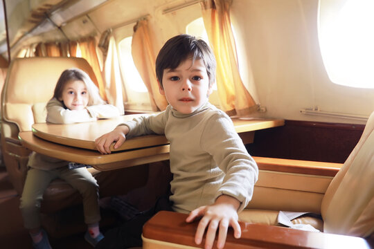 Boy looking at camera while sitting on airplane seat.Kids is resting while sitting in the chair of private business plane
