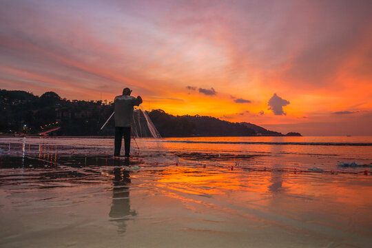 .People come out to trawl their nets on Patong beach during sunset time..