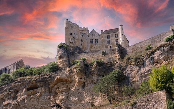 Chateau de Beynac, Beynac castle on the rock against dramatic sunset sky. Village of Beynac-et-Cazenac, Perigord, Dordogne, France.
