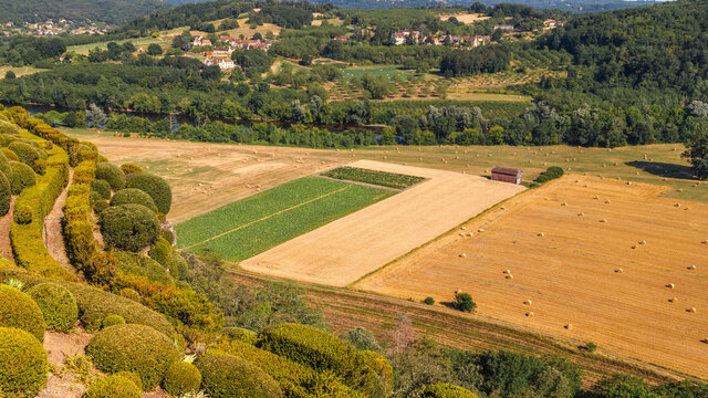 Agricultural landscape in France. Aerial panoramic view of the harvest fields with the round hay bales, green hills and villages in the background.