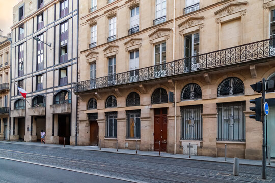 Bordeaux, France. Street in the downtown, tram line and historical house with typical french windows and long balcony.