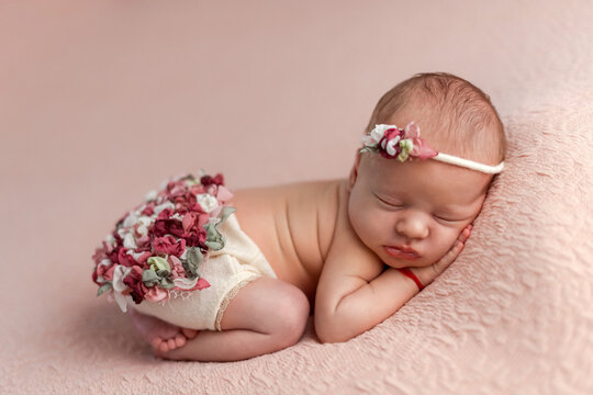 Sleeping newborn girl in the first days of life on pink blanket