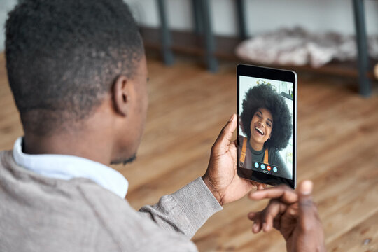 African american man video calling girlfriend on digital tablet. Black couple talking dating by virtual meeting via conference videocall. Remote relationship, online chat concept, over shoulder view.