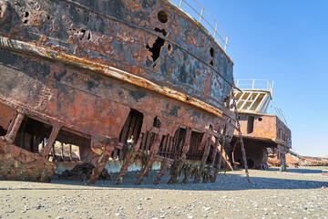 old rusty and rotten ship wreck with holes in its carcass, lying on the beach of the coast line of the Strait of Magellan in Patagonia, south America, abandoned places_4
