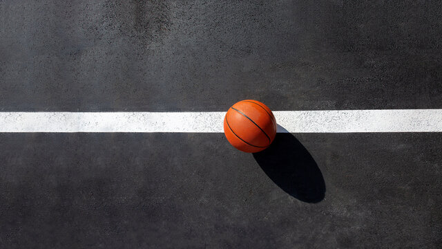 orange striped basketball ball stands on the white line marking the playing field with asphalt tarmac, sports object lit by sun light on playground top view with copy space, nobody.