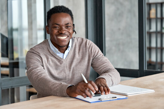 Cheerful african business man wearing headset laughing looking at camera sitting at office table. Happy black male agent, online customer service representative, smiling ethnic manager portrait.