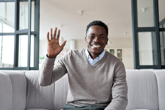 Happy african young man online teacher, coach, distance worker waving hand looking at camera or web cam video conference calling in virtual webcam chat meeting by remote video call. Headshot portrait.