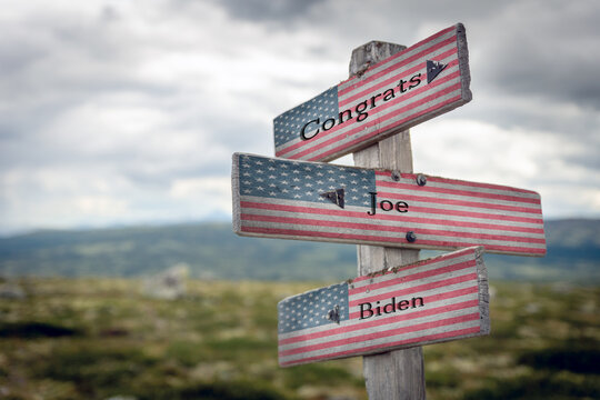 congrats joe biden text on wooden signpost outdoors with the american flag to simulate the 2020 presidential election.