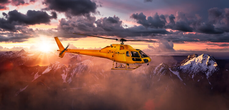 Yellow Helicopter flying over the Rocky Mountains. Dramatic Sunrise. Aerial Landscape from British Columbia, Canada near Vancouver. Composite. Canadian Panoramic Nature Background