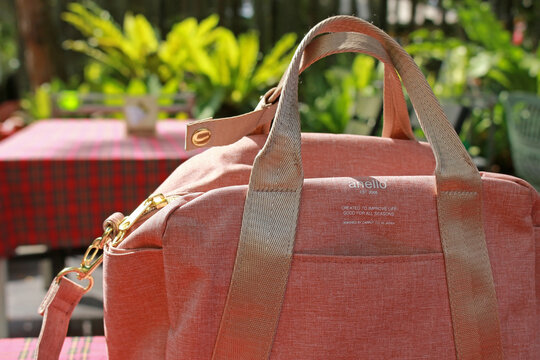 Rayong, Thailand - 8th November, 2020: Close up detail of a pink canvas anello branded handbag outdoors in a sunlit garden setting. Anello is a Japanese bag brand established in 2005.
