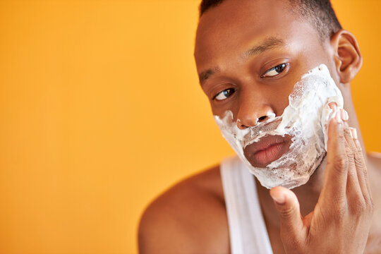 black african man apply foam shaving after shower, do beauty skin procedures, take care of bristle beard in bath, skincare body hygiene concept. isolated yellow background