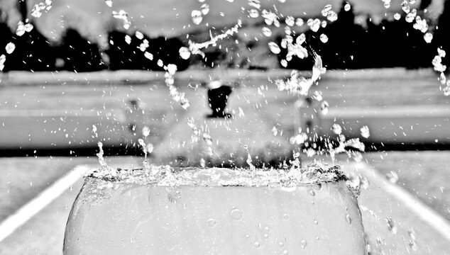 Close up of a water fountain with a wine glass in black and white