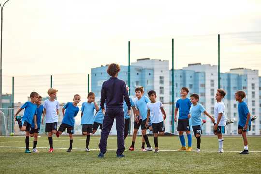 confident football trainer man teach, instruct kids boys in stadium. young caucasian boys attentively listen to him, want to win