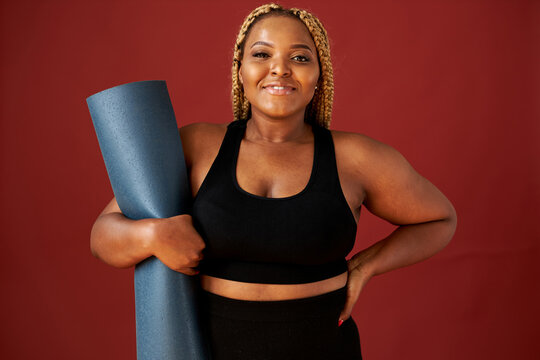 portrait of beautiful chubby african woman going to do sport exercises alone, hold blue mat in hands, posing at camera, wearing black top and leggins