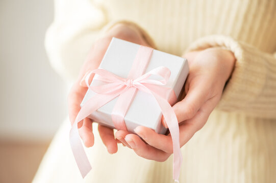 A woman in a sweater gives a gift in a white holiday packaging box with a pink ribbon. Winter festive cozy life style. Romantic present in female hands for christmas, new year