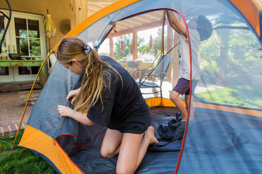 Teenage girl and her younger brother setting up tent to sleep out during a staycation.