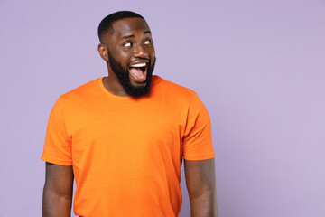 Excited surprised young african american man 20s wearing basic casual orange blank empty t-shirt standing keeping mouth open looking aside isolated on pastel violet colour background, studio portrait.