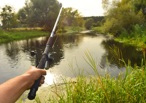 Line fishing with a fishing rod on a beautiful river in Brandenburg, Germany