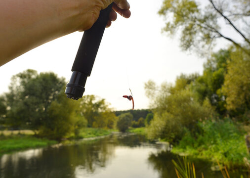 Line fishing on a river hand holding a fishing rod with a worm