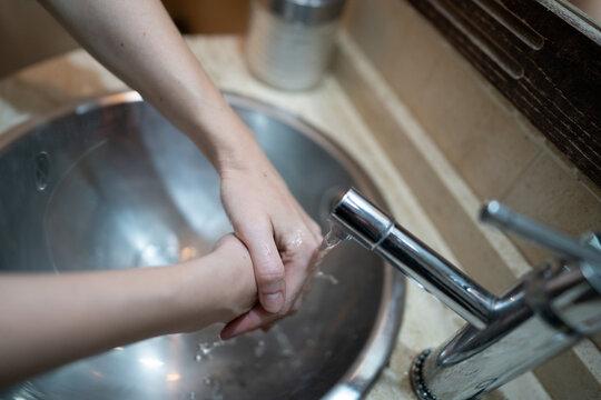 Mujer se lava las manos en el baño. Medidas para prevenir covid19