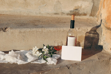 Mediterranean summer wedding still life composition. Blank paper greeting card mockup scene with red wine bottle, drinking glass and white oleander flowers. Sandstone ground and stairs in sunlight.