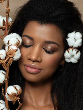 Young beautiful woman with cotton flowers