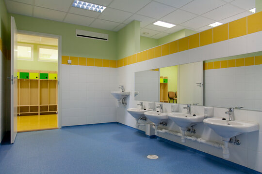 School Restroom, modern style with yellow paint and blue flooring