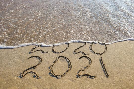 2020, 2021 years written on sandy beach sea. Wave washes away 2020.