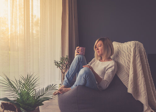 pensive woman drinking coffee at home