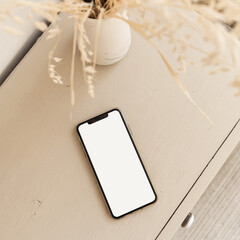 Blank screen smart phone on beige pastel table. Flat lay, top view. Copy space mockup template.