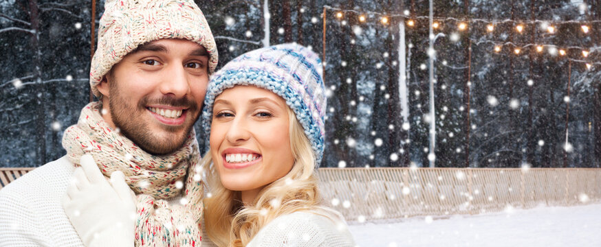 christmas, winter holidays and people concept - happy couple hugging over outdoor ice skating rink background