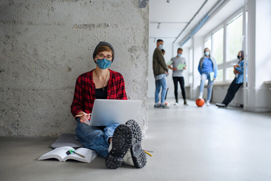 Young student with laptop sitting on floor back at college or university, coronavirus concept.