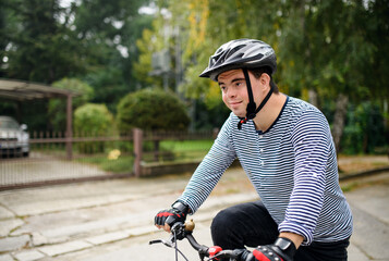 Portrait of down syndrome adult man with bicycle cycling outdoors on street.