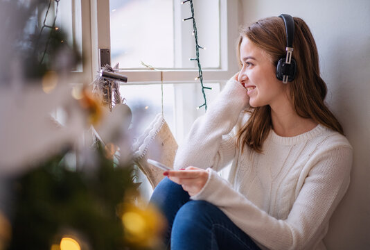 Portrait of young woman indoors at home at Christmas, using smartphone and headphones.