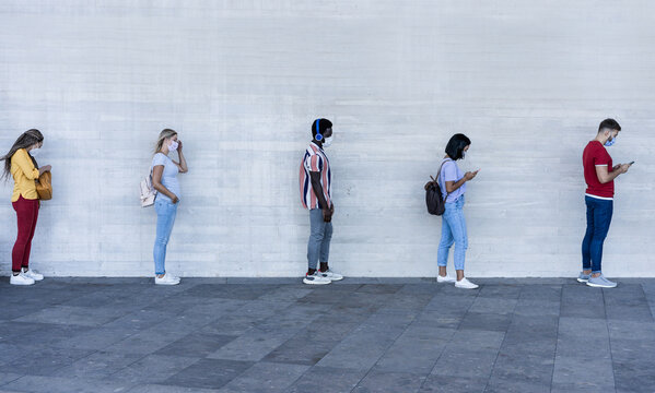 Group of young people waiting for going inside a shop market while keeping social distance in line during coronavirus time - Protective face mask and spread virus prevention -  Main focus on black man