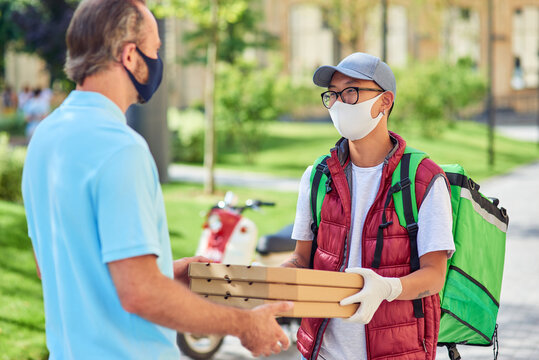 Young asian courier wearing face protective mask and gloves giving boxes with pizza to customer while standing on a sunny street. Food delivery during coronavirus pandemic