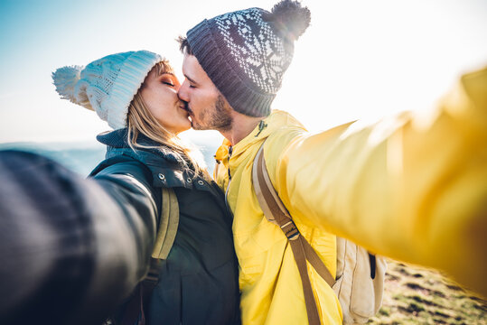 Hikers taking a selfie on the top of the mountain - Couple in love kissing outdoor - Bright filter