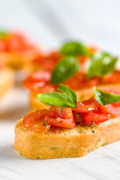 Detail of bruschetta: traditional italian appetizer with tomatoes, basil leaves and olive oil.