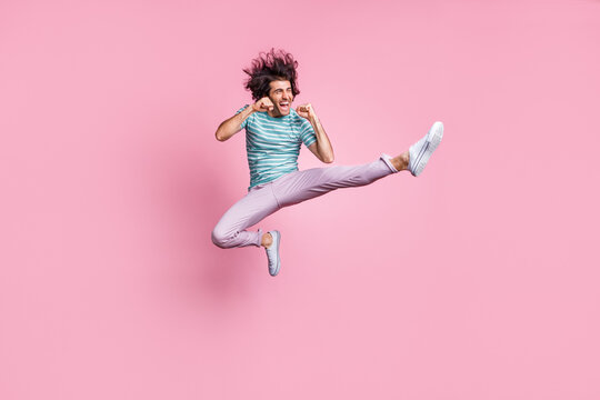 Full length photo of handsome young guy dressed casual clothes jumping fighting isolated pastel color background