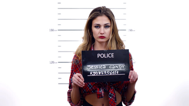Young prostitute with signboard mug shot in police station