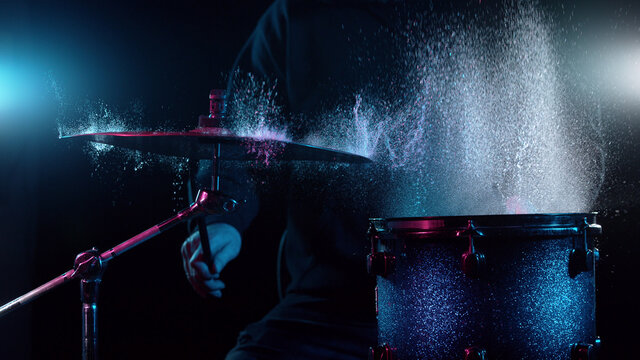 Freeze motion of drummer hitting drums with water splashes