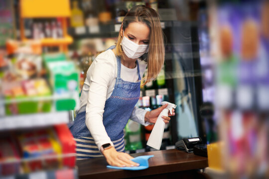 Shop assistant disinfecting surfaces in grocery store