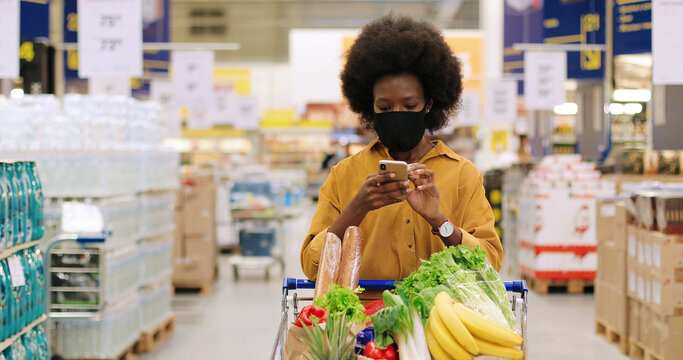 Portrait of African American young beautiful female customer in mask in supermarket with shopping cart full of food products and texting on smartphone. Woman typing on cellphone in grocery.