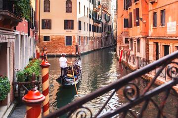 Venetian gondolier takes tourists on gondola ride down quiet narrow canal through Venice, romantic trip