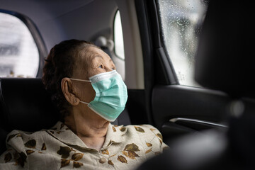 Elder woman using protective face mask during traveling. Coronavirus or COVID-19 pandemic concept. COVID19 outbreak.
