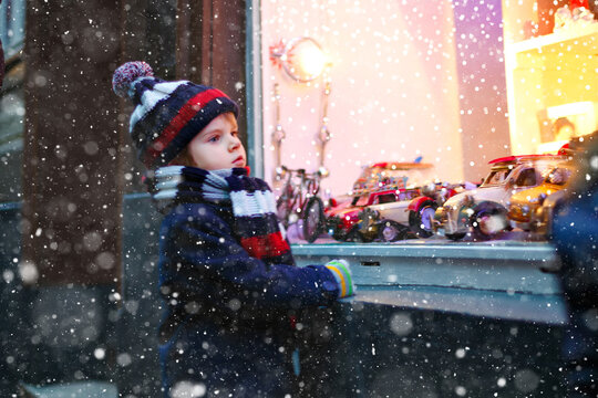 Cute toddler boy looking on car toys in a window on Christmas time season. Fascinated child in winter clothes dreaming and wishing. Window decorated with xmas gifts. Snow falling down, snowfall.