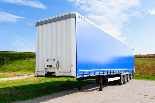 Brand new blue truck trailer waiting  by the road in a field, on  a bright summer day